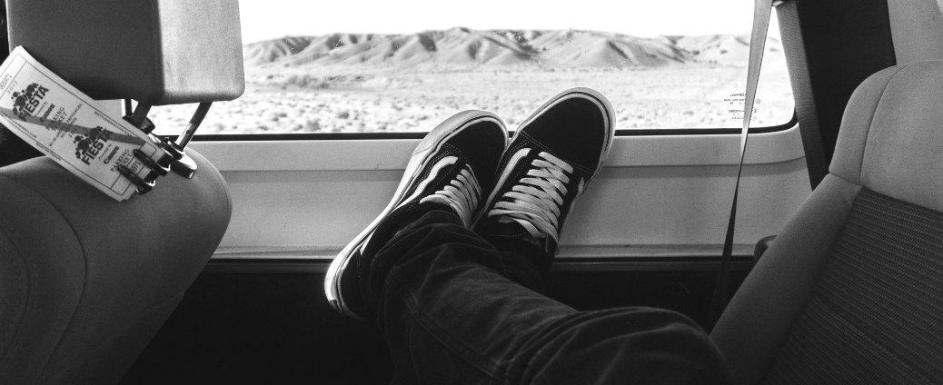 road trip viaggio strada deserto scarpe sul finestrino